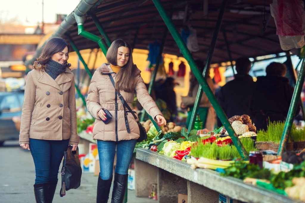 Two women walking in the farmer's market in winter