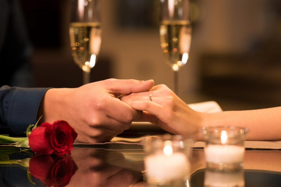 Couple holding hands at a romantic restaurant